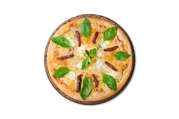 Pizza italiana tradicional con salchichas ahumadas, mozzarella y albahaca sobre plancha de madera aislada