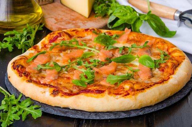 Pizza italiana tradicional con salsa de tomate, salmón ahumado y rúcula fresca sobre una piedra oscura.