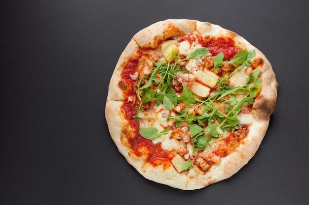 Pizza con jamón ahumado y rúcula sobre fondo negro. sabrosa pizza italiana fina con carne en el suelo oscuro-vista superior plana laical