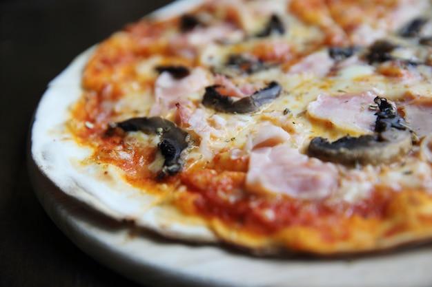 Pizza de jamón y champiñones sobre madera