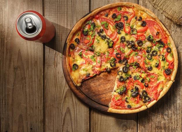 Pizza y lata de bebida en la vista superior de la mesa