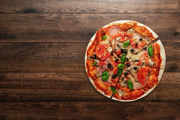Pizza en madera con jamón, aceitunas, tomate y albahaca verde