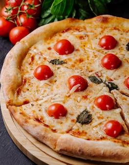 Pizza margarita con tomates cherry y hojas basílicas.