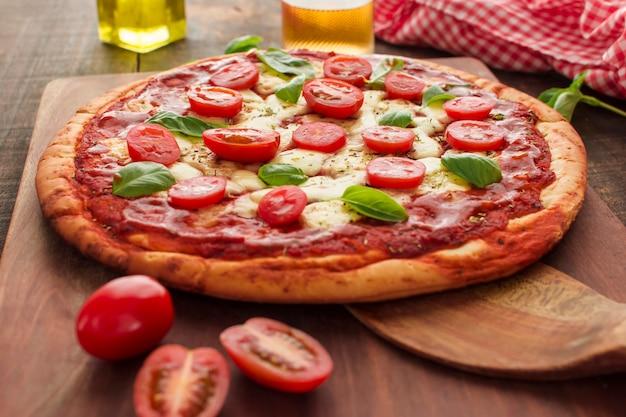 Pizza de margherita casera en tabla de cortar de madera