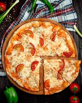Pizza margherita con rodajas de limón en una bandeja de madera