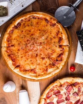 Pizza margherita con saleros y pimenteros sobre la mesa
