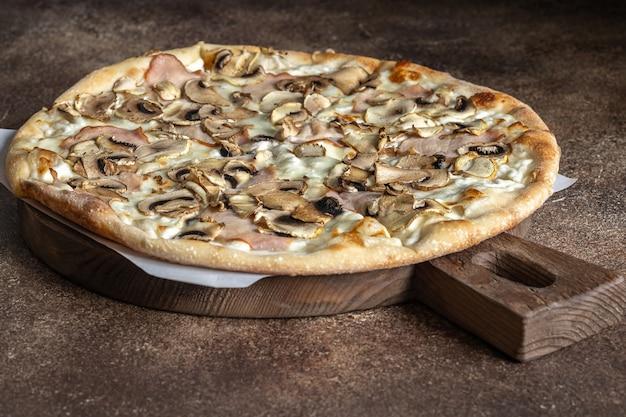 Pizza de masa fina con champiñones y jamón sobre la plancha de madera en marrón oscuro