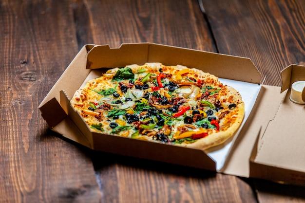 Pizza mediterránea con aceitunas y queso en cartón sobre mesa de madera
