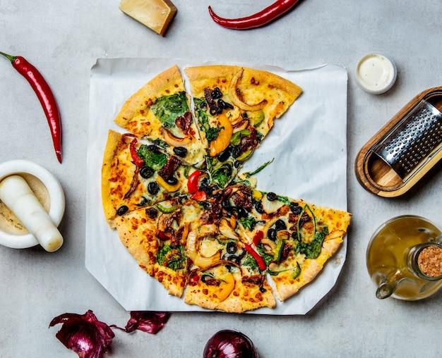 Pizza mediterránea con aceitunas y queso e ingredientes alrededor