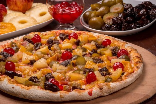 Pizza de melocotón, cereza, ciruela, higo y piña en una tabla de madera. pizza dulce brasileña.