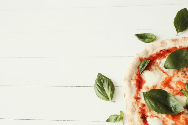 Pizza en mesa de madera blanca