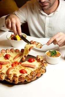 Pizza mixta con salchichas y tomate