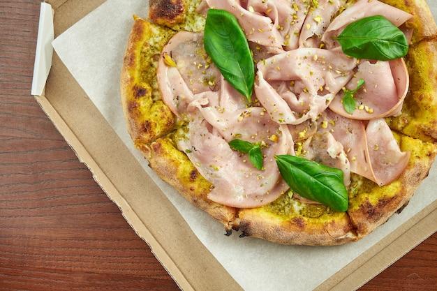 Pizza con mortadela, pistachos, albahaca y queso derretido en una caja de cartón con salsa lateral en una mesa de madera