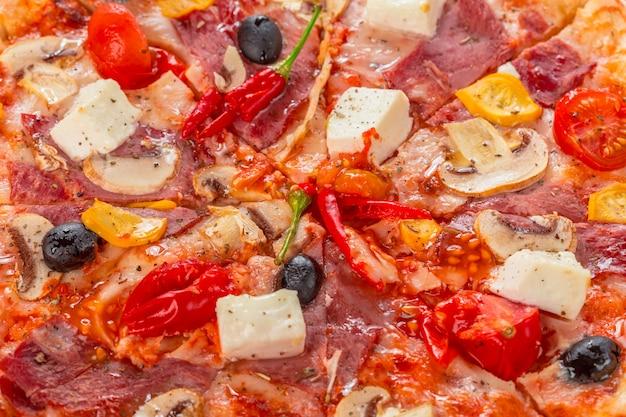 Pizza con mozzarella, jamón, tomates cherry, aceitunas negras