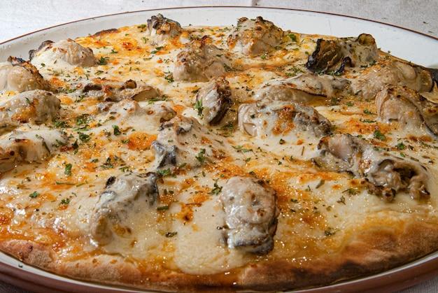 Pizza con mozzarella de sabor especial con ostras y finas hierbas servidas en una placa blanca.