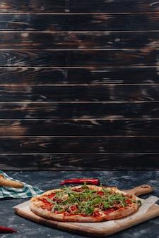 Pizza napolitana apetitosa picante a bordo con tomates cherry y chile, espacio libre para texto