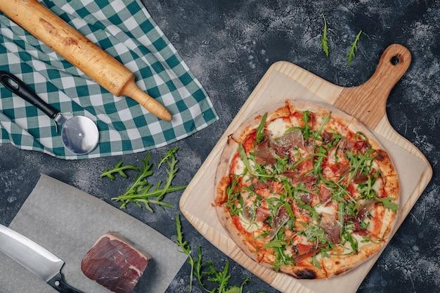 Pizza napolitana deliciosa en una pizarra con varios ingredientes, espacio libre para texto