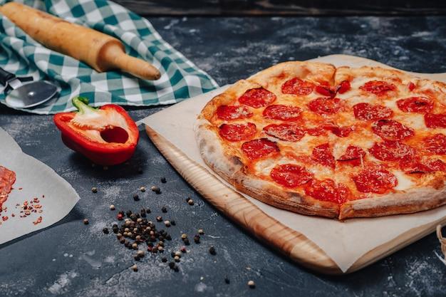 Pizza napolitana deliciosa en una pizarra con varios ingredientes