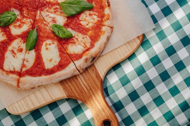 Pizza napolitana con jamón, queso, rúcula, albahaca, tomates espolvoreados con queso en una tabla de madera