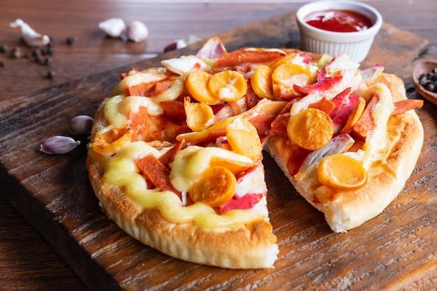 Pizza de pan plano en tablero de pizza de madera