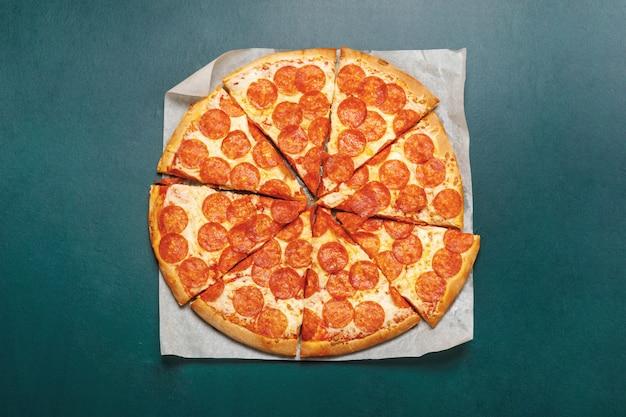 Pizza peperoni en pizarra verde.