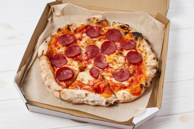 Pizza de pepperoni en una caja sobre una mesa de madera blanca
