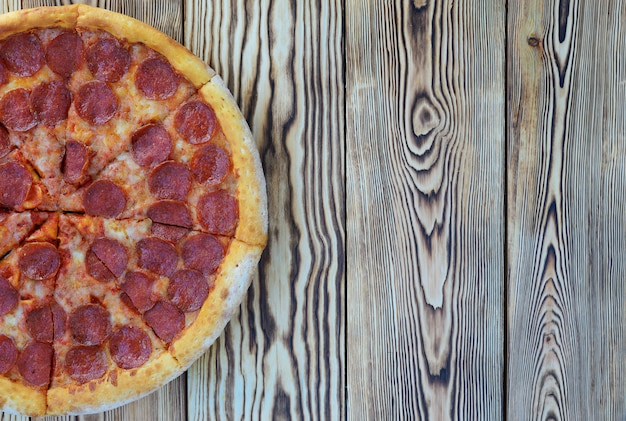 Pizza de pepperoni con espinacas sobre un fondo de madera