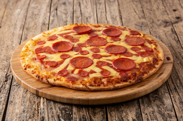 Pizza de pepperoni italiana en mesa de madera