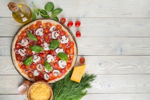 Pizza en la piedra para hornear pizza e ingredientes de pizza en una vista superior de fondo de madera