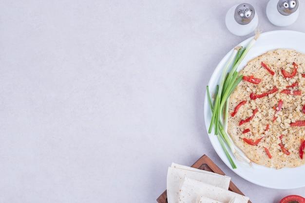 Pizza con pimientos y cebolla en plato blanco.
