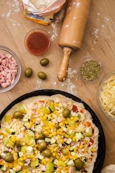 Pizza plana sin cocer en una sartén con ingredientes