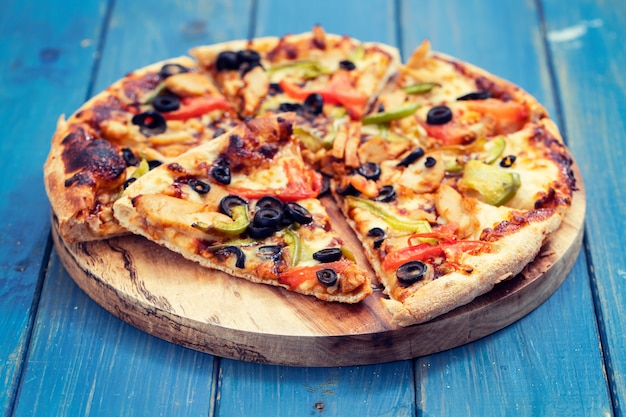 Pizza con pollo y aceitunas sobre superficie de madera azul