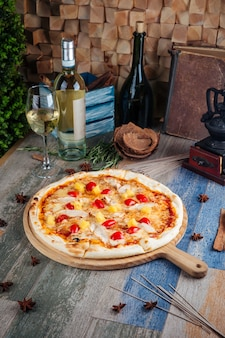 Pizza de pollo y piña con tomates cherry