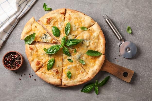 Pizza de queso con albahaca, cortador y especias sobre fondo gris