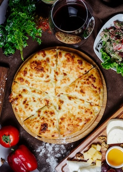Pizza con queso tomate y pimiento sobre la mesa