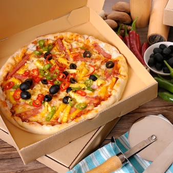 Pizza recién horneada en caja de entrega con ingredientes.