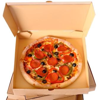 Pizza recién horneada con pila de cajas de entrega