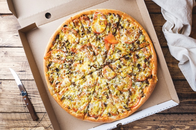 Pizza recientemente cocida en una caja de cartón en una tabla de madera.