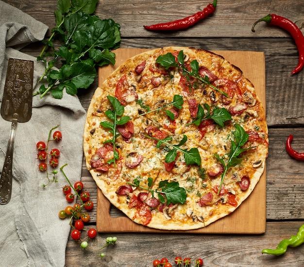 Pizza redonda al horno con salchichas ahumadas, champiñones, tomates, queso y hojas de rúcula