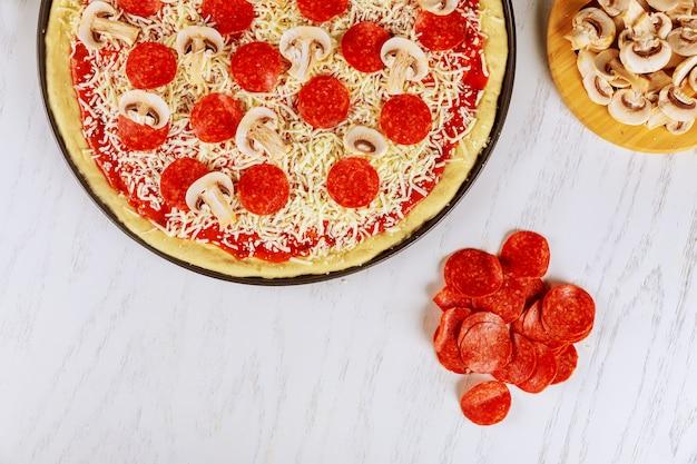 Pizza redonda sin cocer con pepperoni y champiñones