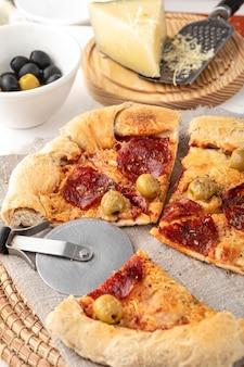 Pizza en rodajas con cortador al lado