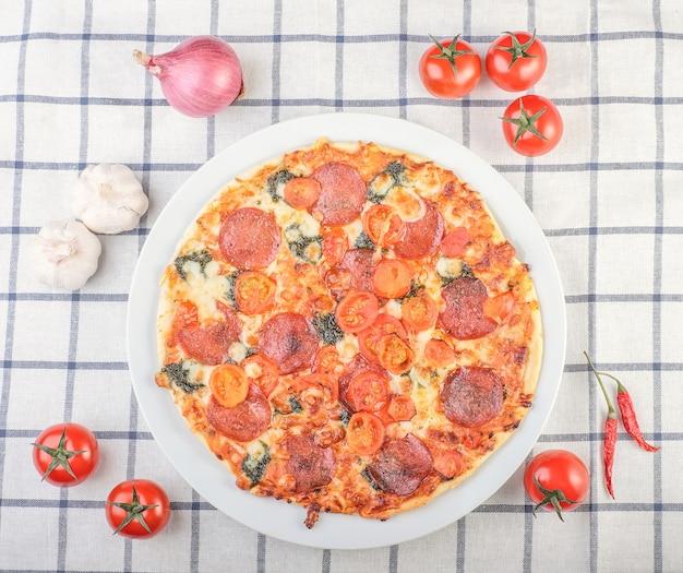 Pizza rodeada de ingredientes tomates, cebolla, pimiento sobre la mesa