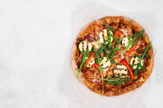 Pizza de rúcula con fondo blanco.