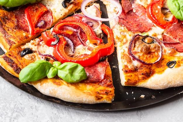 Pizza con salami, cebolla, pimiento, aceitunas, mozzarella y albahaca. pizza casera de pepperoni caliente.