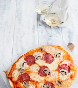 Pizza con salami y champiñones sobre un fondo blanco de madera y dos copas de vino blanco
