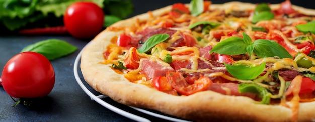 Pizza con salami, jamón, tomate, queso y champiñones.