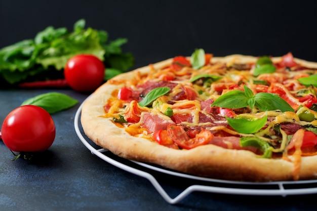 Pizza con salami, jamón, tomate, queso y champiñones
