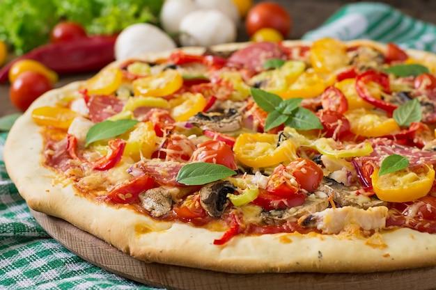 Pizza con salami, tomate, queso y champiñones.