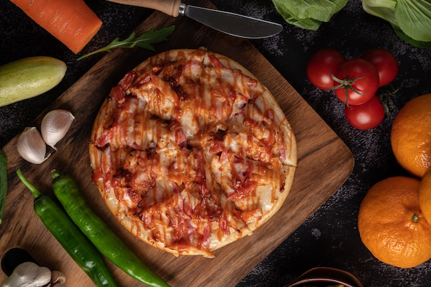 Pizza con salchicha, maíz, frijoles, camarones y tocino en una placa de madera