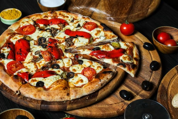 Pizza con salchichas, tomate, queso, aceitunas y pimiento